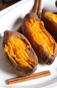 Three cooked sweet potatoes on a platter with cinnamon sicks.