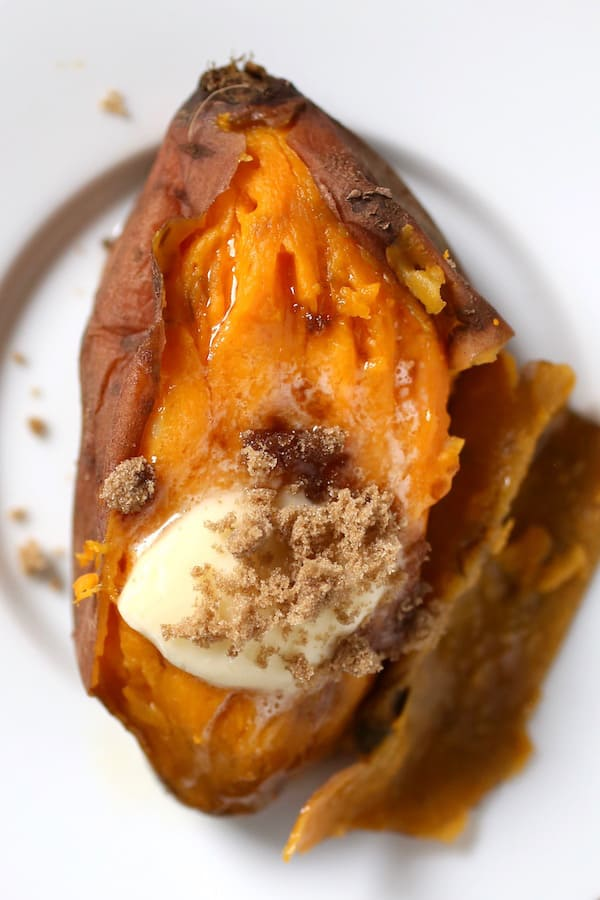 Sweet potato topped with butter and brown sugar on white plate.