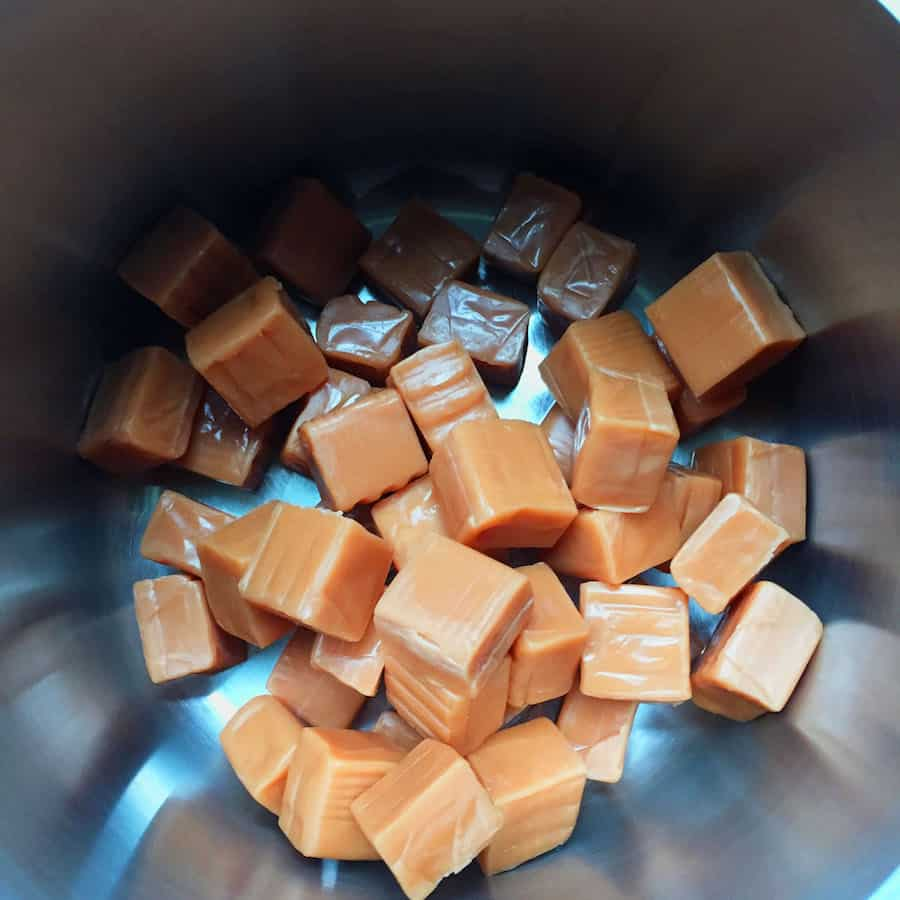 Unwrapped caramel candies in the bottom of a pot.