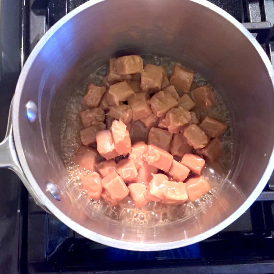 Caramel candies melting in a pot. Bubbles appear on the edge of the pan.