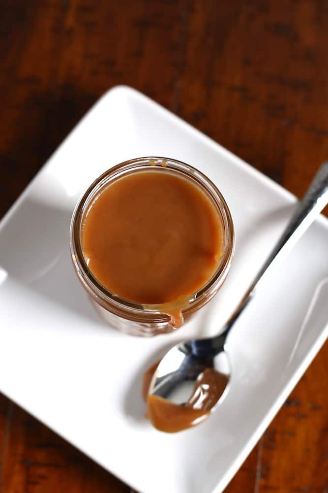 Caramel sauce in a jelly jar on a white plate with a spoon sitting next to it.