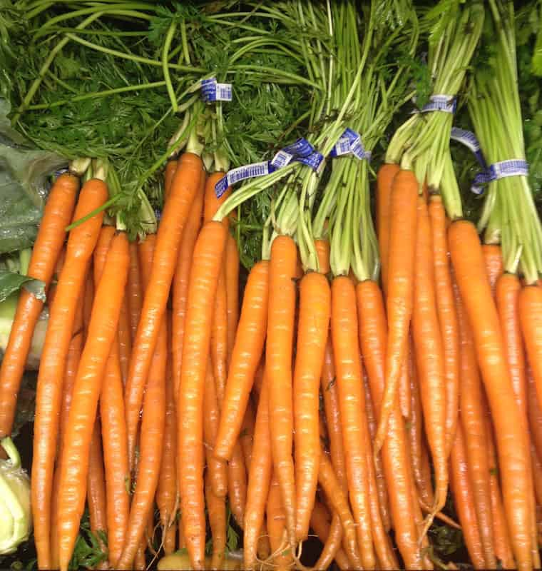 Carrots with steams attached on grocery store shelf.