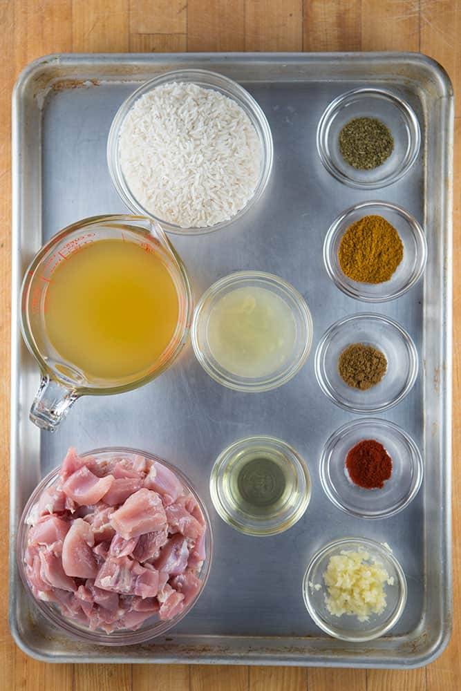 Ingredients for pressure curry chicken on a baking sheet. Raw chicken. Chicken broth. Rice and spices.
