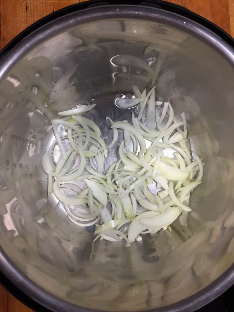 Onion slices cooking in a pressure cooker pot.