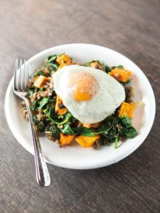Egg cooked over-medium sits atop sweet potato hash with spinach and sausage.