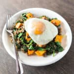 Over medium egg sits atop a plate of sweet potato hash with spinach and sausage.