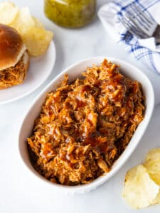 Serving dish with barbecue pulled chicken. On the side is a pulled chicken sandwich on a plate with potato chip.