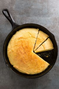 Skillet cornbread in pan. Two pieces are sliced.