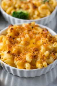 Small bowls of macaroni and cheese topped with melted cheese and breadcrumbs.