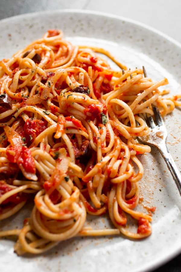 Pasta with tomato sauce and olives on a plate.