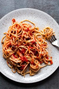 Pasta with tomatoes and olives in a gray speckled plate.