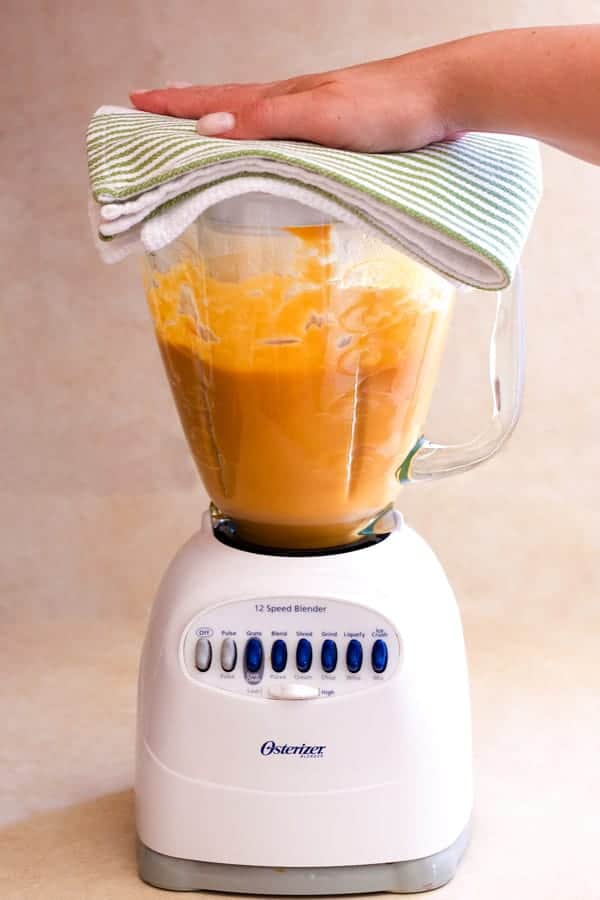 Blender filled with pureed soup. A hand hold the lid on the blender.