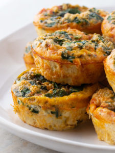 Baked Egg Cups with Spinach Stacked on a Plate.