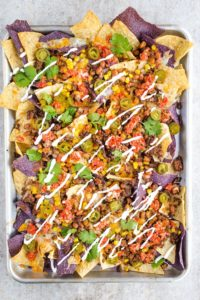 Sheet Pan with Baked Nachos. Topped with Cooked Ground Beef, Corn, Salsa, Drizzled Sour Cream, Beans, and Chopped Cilantro.