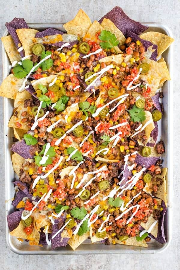 Sheet Pan with Baked Nachos. Topped with Cooked Ground Beef, Corn, Salsa, Drizzled Sour Cream, Beans, and Chopped Cilantro