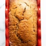 Brown sugar banana bread in red loaf pan.