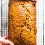 Hands place a brown sugar banana bread onto a cooling rack.