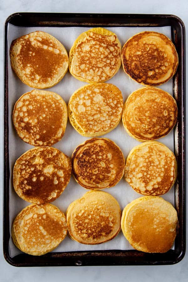 12 cornmeal pancakes on a sheet pan