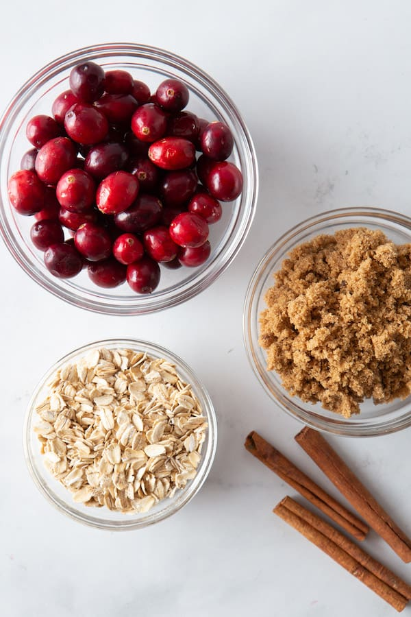 Bowl of Fresh Cranberries. Bowl of Oats. Bowl of Brown Sugar. Three cinnamon sticks.