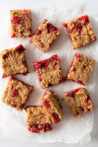 Cut cranberry oatmeal bars on parchment paper