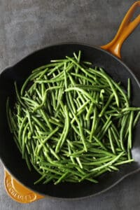 Cooked green beans in a skillet.