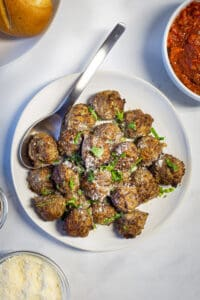 Plate of air fryer meatballs. Topped with chopped basil and sprinkled with cheese. A bowl of sauce and a bowl of grated cheese are alongside the meatballs.