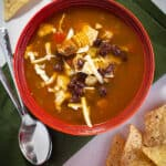 Bowl of tortilla soup in a red bowl sitting on a green placemat. Tortilla chips are on the table near the bowl.