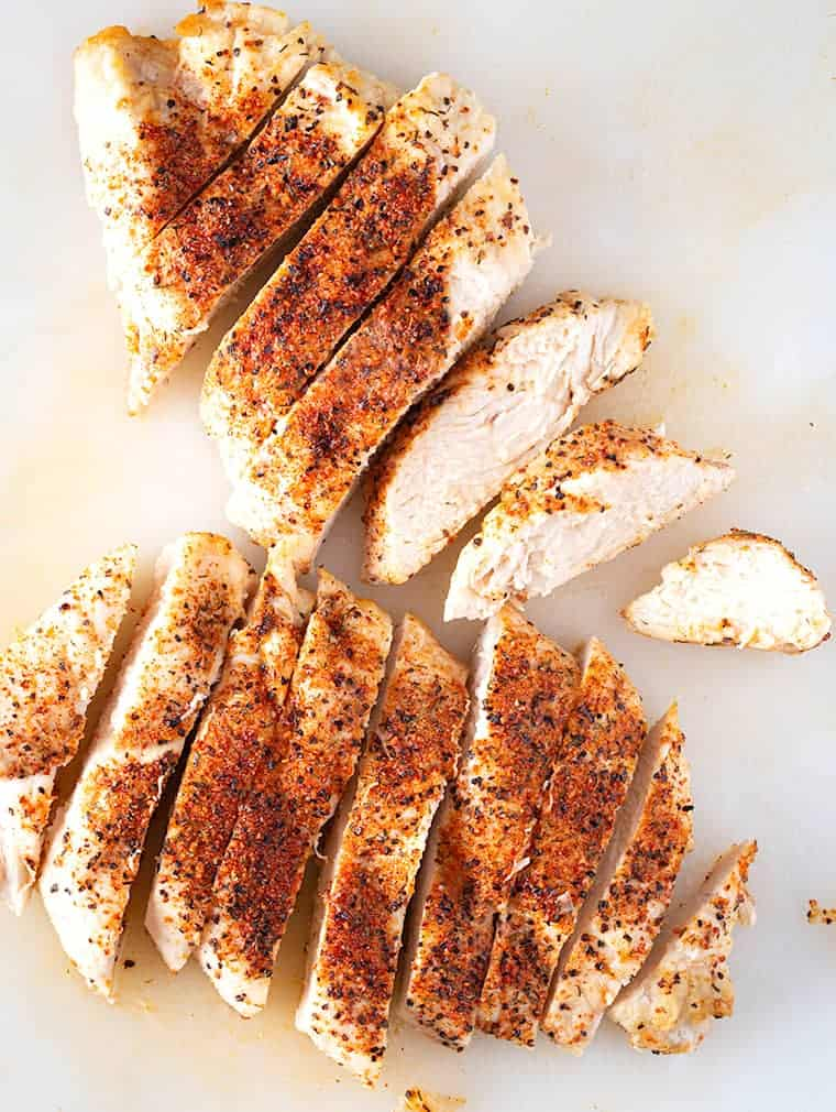 Air fryer chicken breast, cooked and sliced on cutting board.