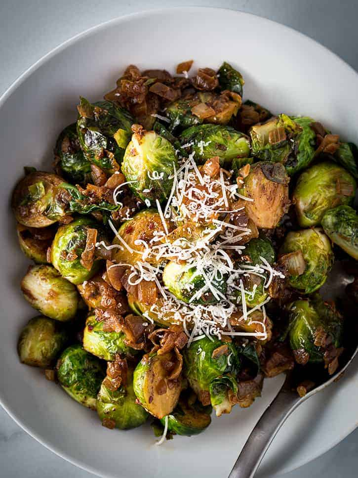 Bowl of Sauteed Brussels sprouts topped with parmesan cheese.