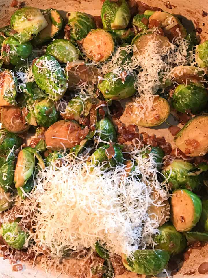 Cooked Brussels sprouts topped with freshly grated parmesan cheese.