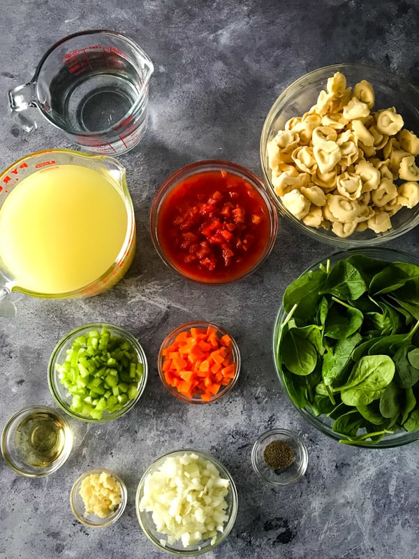 Ingredients for tortellini soup measured and in glass bowls.
