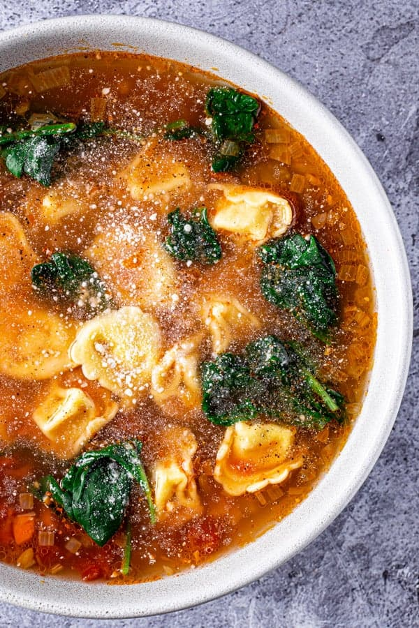 Bowl of tortellini soup with spinach topped with grated parmesan cheese.