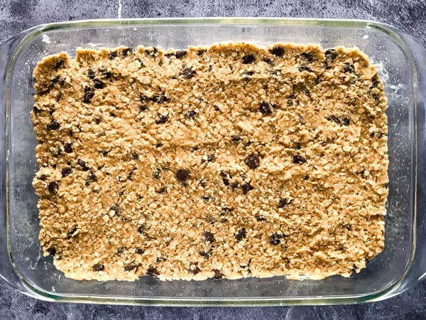 Oatmeal chocolate chip cookie dough pressed into a 9x13-inch pan.