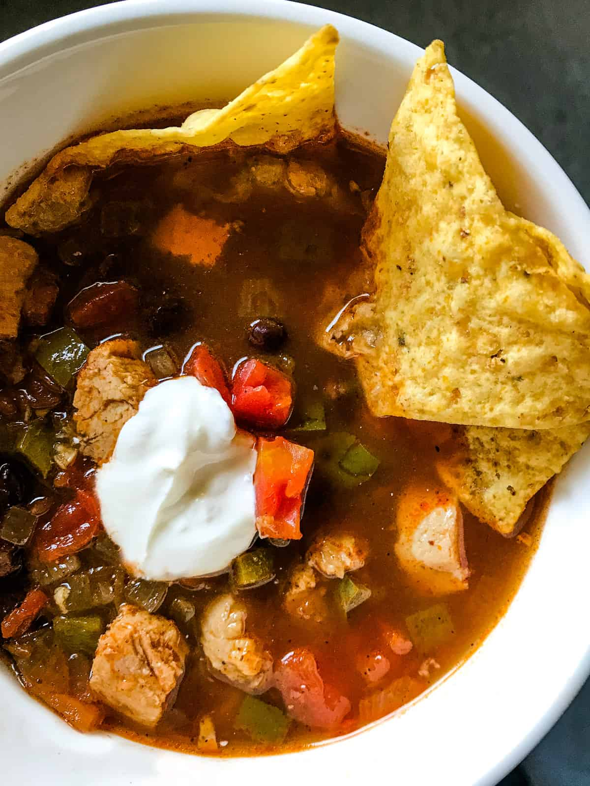 Chicken tortilla soup in white bowl with tortilla chips.