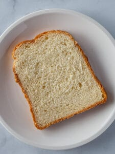 Large slice of sandwich bread on a small white plate.