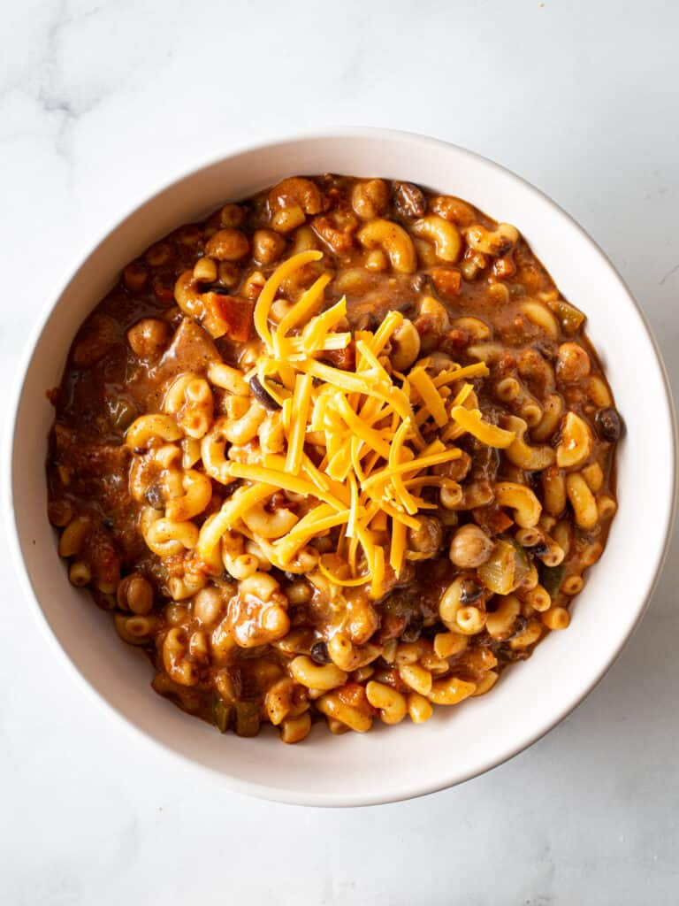 Chili Mac in a white bowl topped with grated Cheddar cheese.