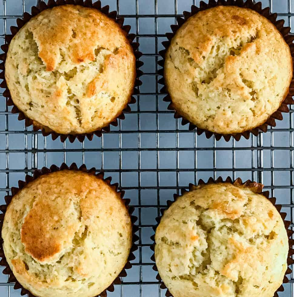 Four baked banana muffins on a cooling rack.