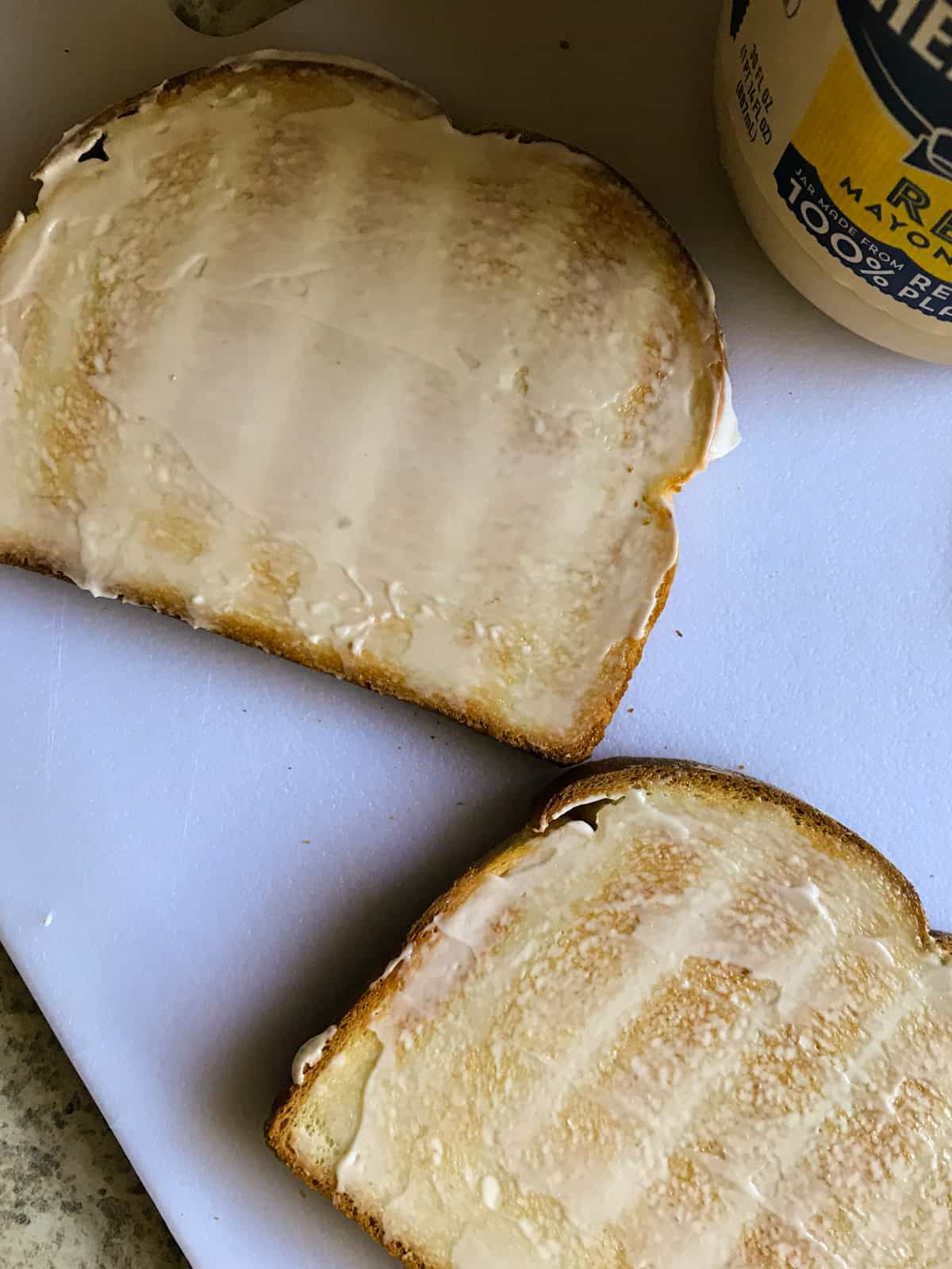 Mayonnaise spread on grilled bread.