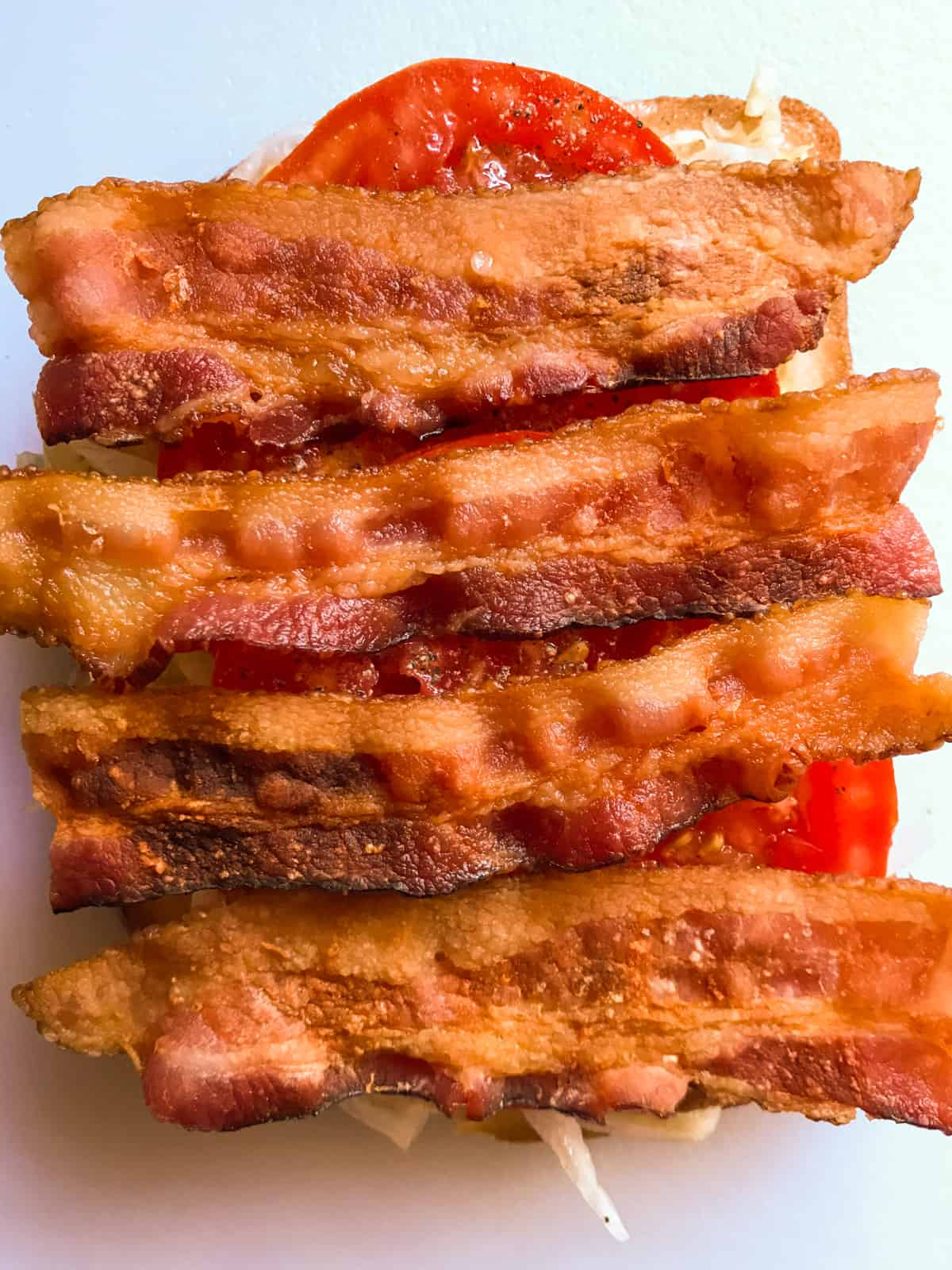 Four slices of bacon on BLT sandwich.