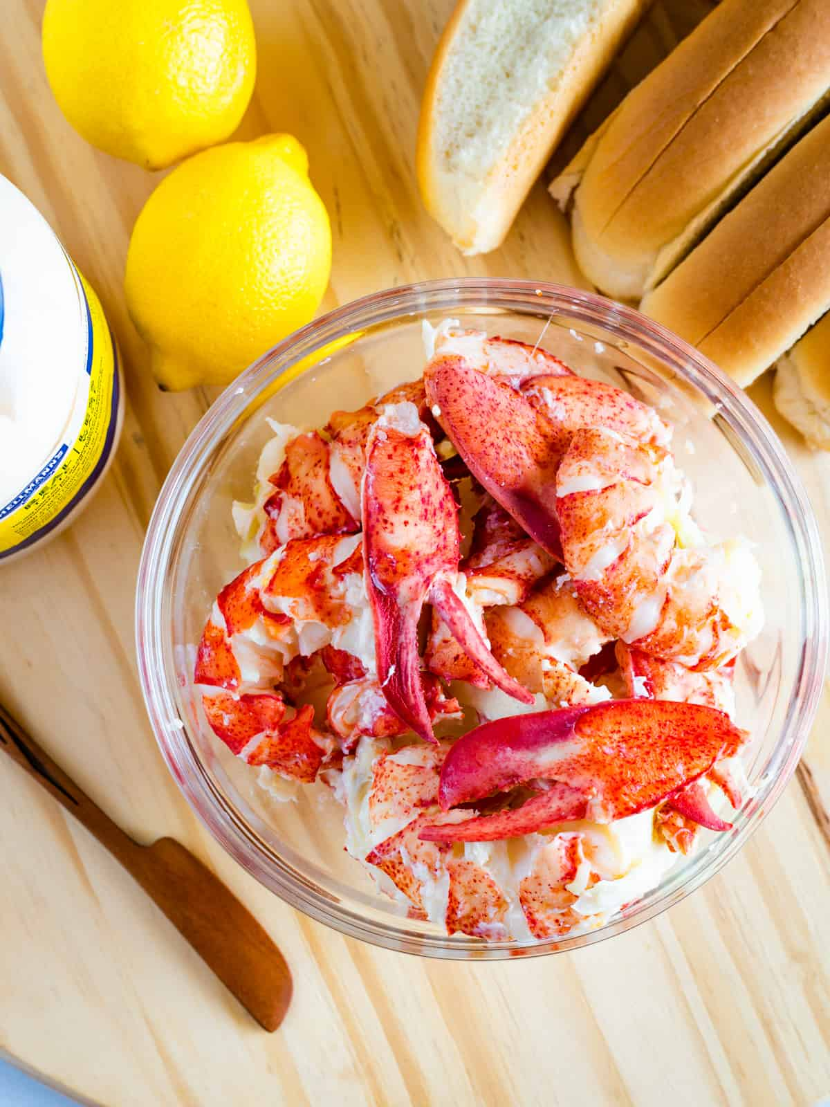 Bowl of lobster meat. Lemons. Hot dog buns and mayo.