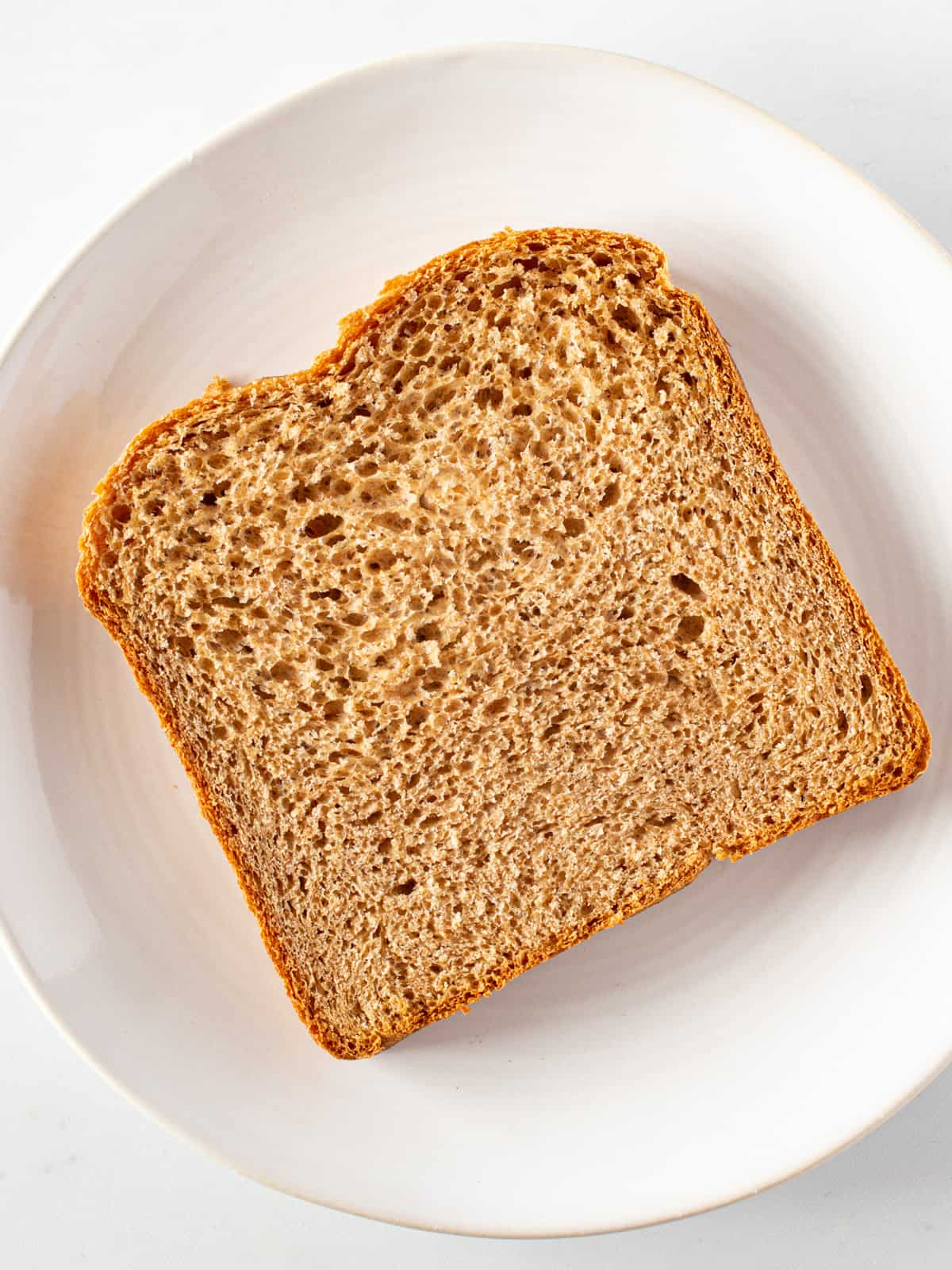 Whole wheat slice of bread on plate.