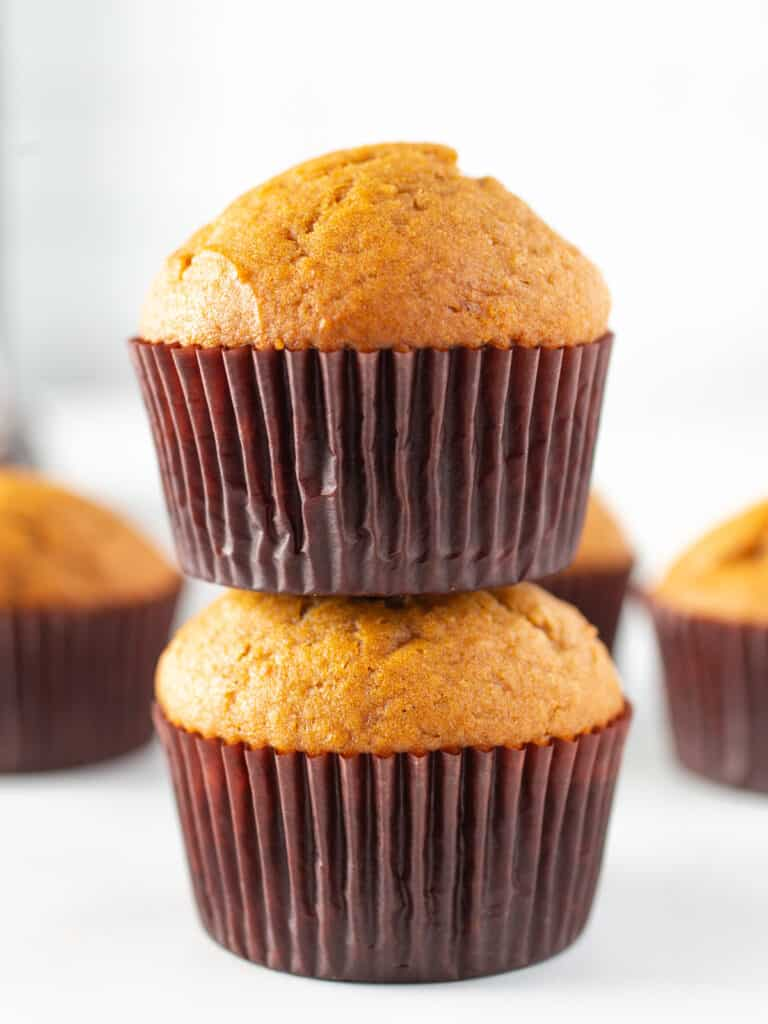 Two pumpkin muffins stacked on each other.