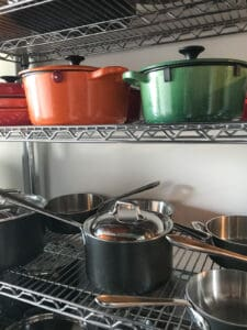 Two shelves full of pots and pans.