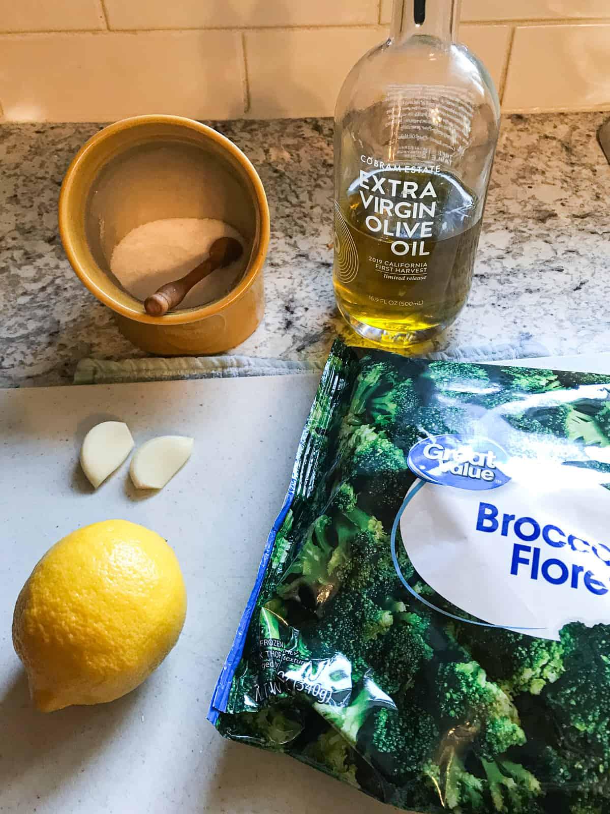 Ingredients for cooking frozen broccoli. Salt, olive oil, bag of broccoli florets, lemon, and two cloves of garlic.