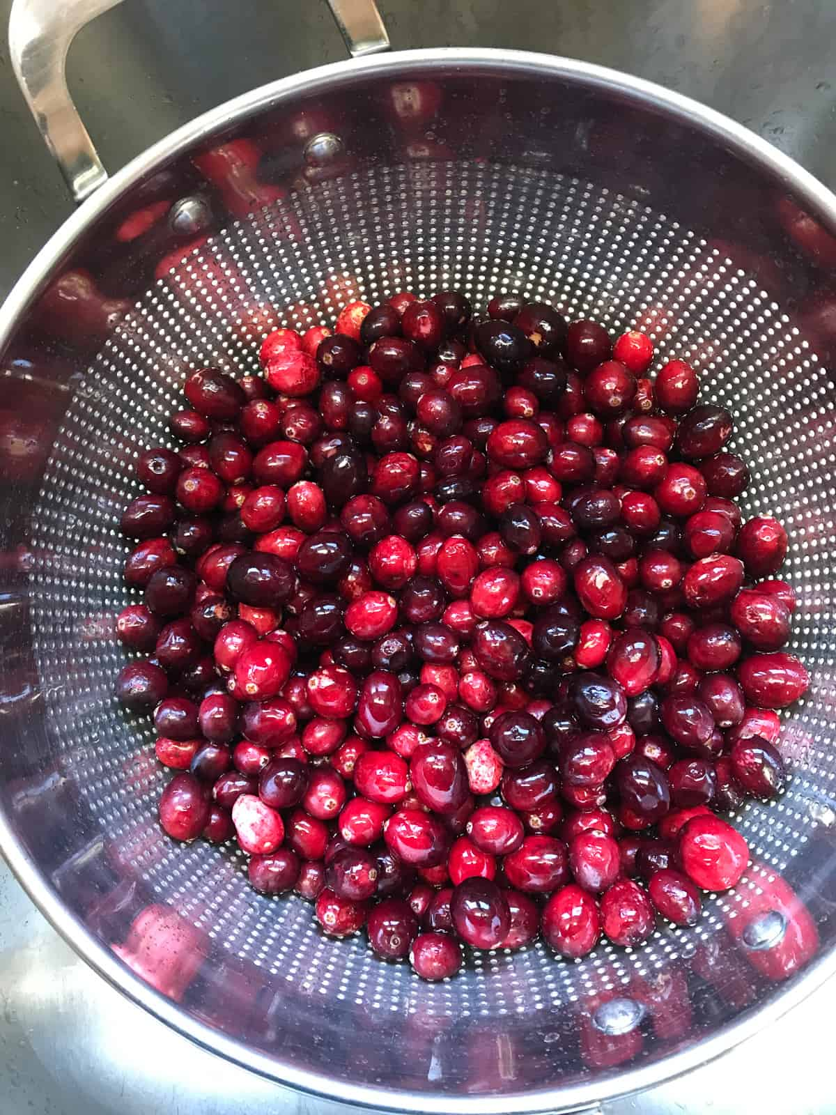 Washing cranberries in a colander.
