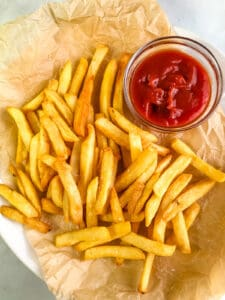 Air fryer cooked French fries on a platter with a small bowl of ketchup.