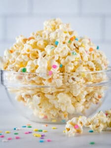 White chocolate popcorn with colorful sprinkles in a glass bowl.