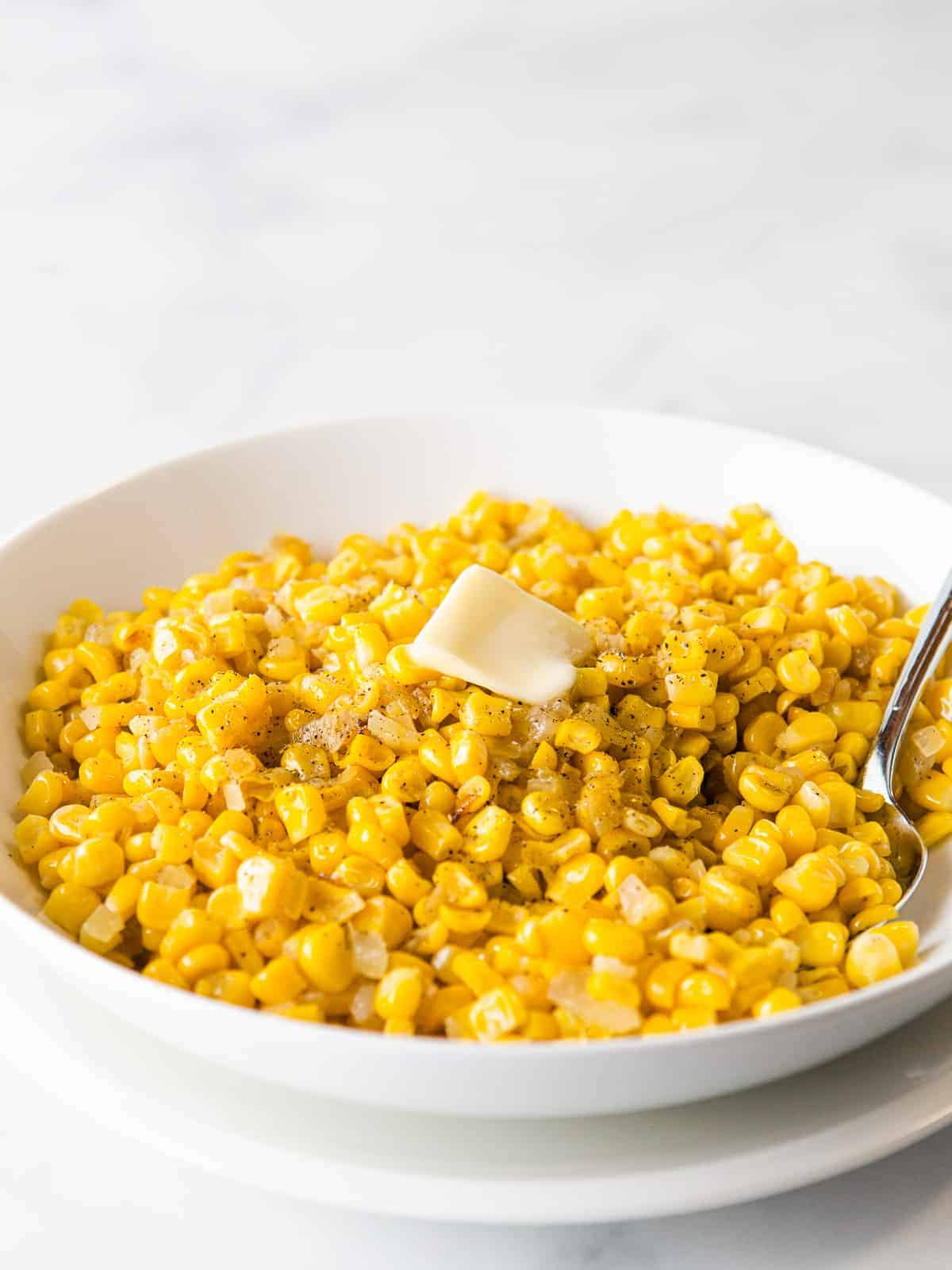 Cooked frozen corn with onions and black pepper, topped with butter, in a white bowl.