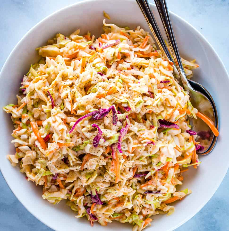 Easy coleslaw in a white bowl with two servings spoons alongside.