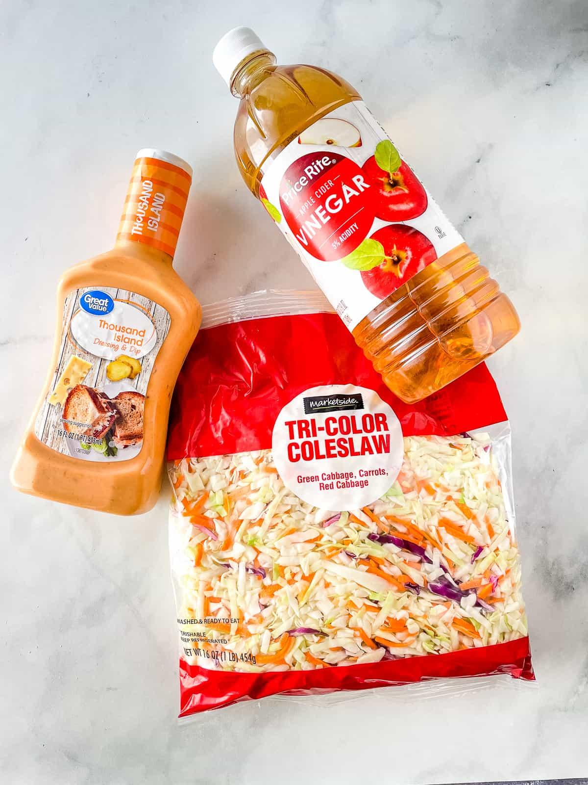 Ingredients for easy coleslaw. Bottle of dressing. Bottle of cider. Bag of coleslaw mix.